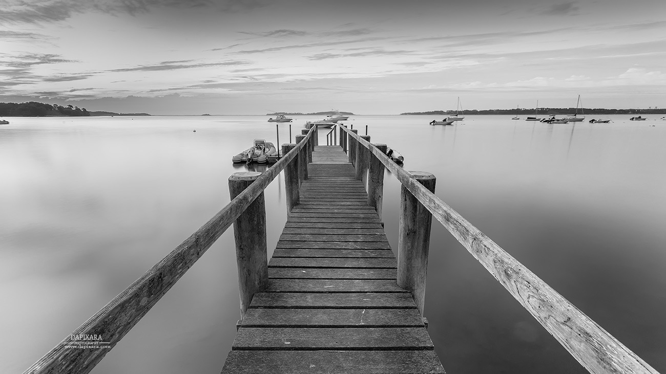 Black and white panorama photograph of boat dock at sunrise on pleasant bay